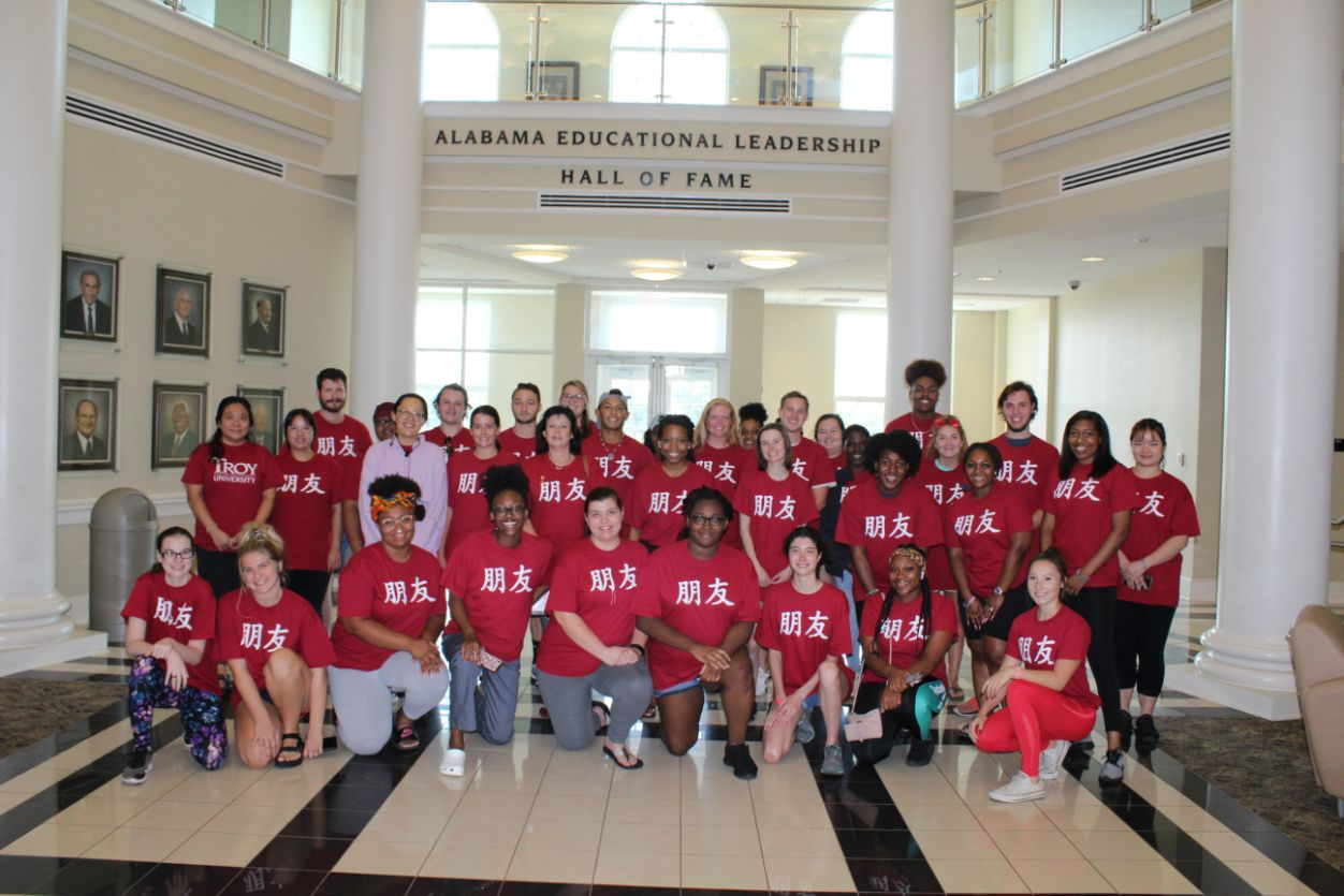 "Dr. Hooten's students pose with the CIT scholars in Hawkins Hall for a group picture, wearing Troy shirts that read ""friend"" in Chinese."