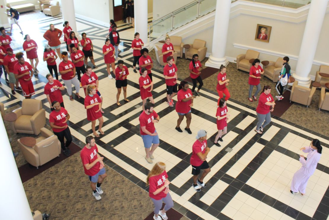 Around 30 students stand in Hawkins Hall practicing Tai Chi movements such as shaping a ball between their hands and bending their knees, led by He Jing.