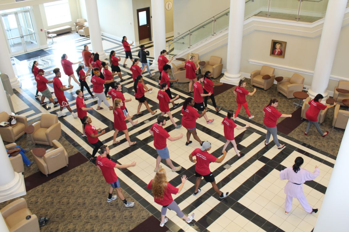 The students move in a sequence of steps, practicing Tai Chi with their legs and arms separated and angled in a fighting stance.