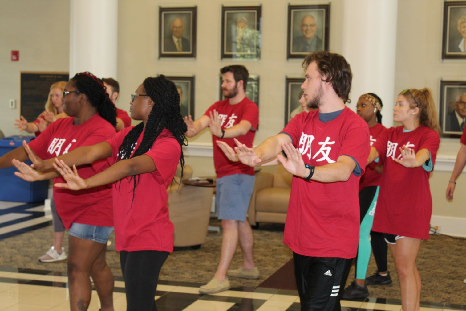 The students move into another Tai Chi sequence with their arms outstretched in front of them and their legs spread.