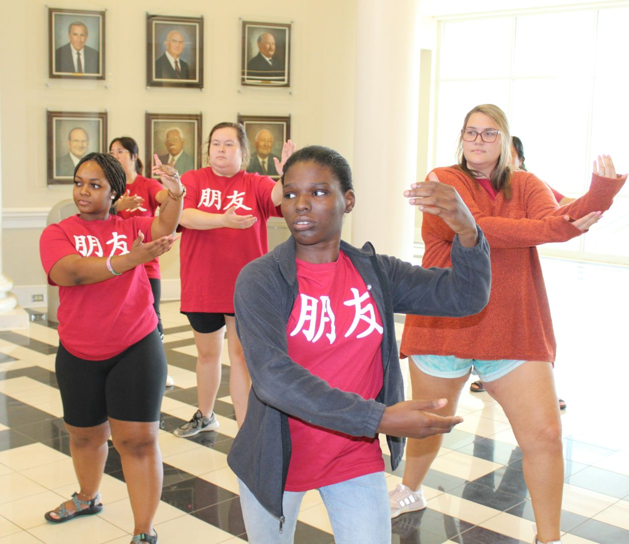 Male students gather to practice the Tai Chi movement that places their right hand on their left elbow in an L-shape.
