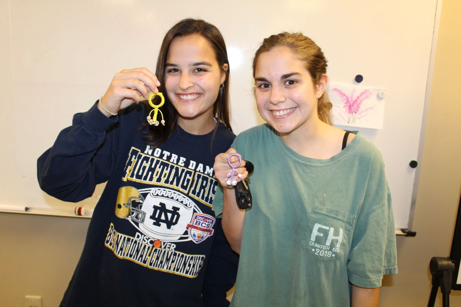 Two students pose together proudly displaying their newly made key chains.