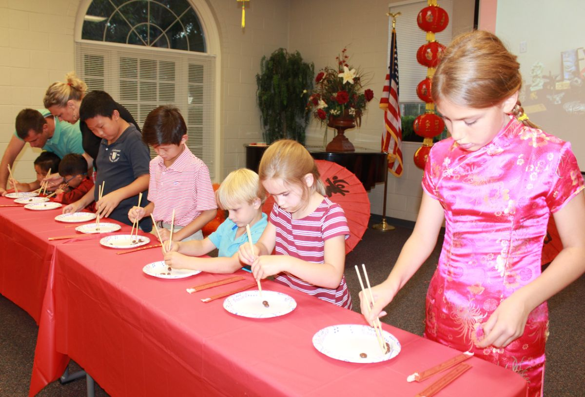 Parents and children work together to move beans using chopsticks in family-oriented game.