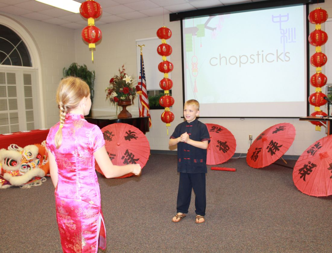 "The children play a round of ""Act and Guess,"" in which they try to get their partner to guess which term- such as chopsticks- they are acting out."