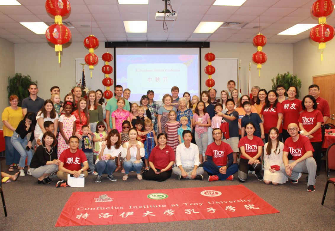 The guests and hosts of the Mid-Autumn Festival Celebration pose together for a group picture.