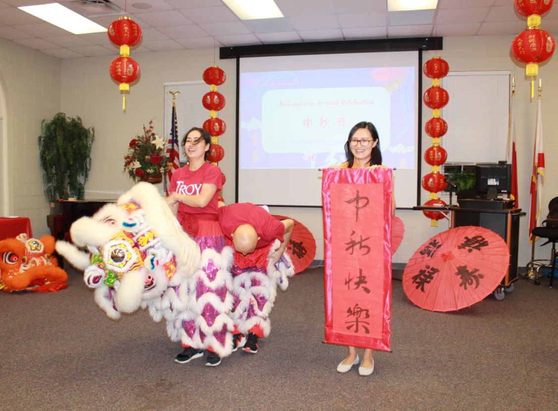 "The CIT Visiting Scholars pose in Lion Dance garb and hold up a banner that says, ""Happy Mid-Autumn Festival"" in Chinese."