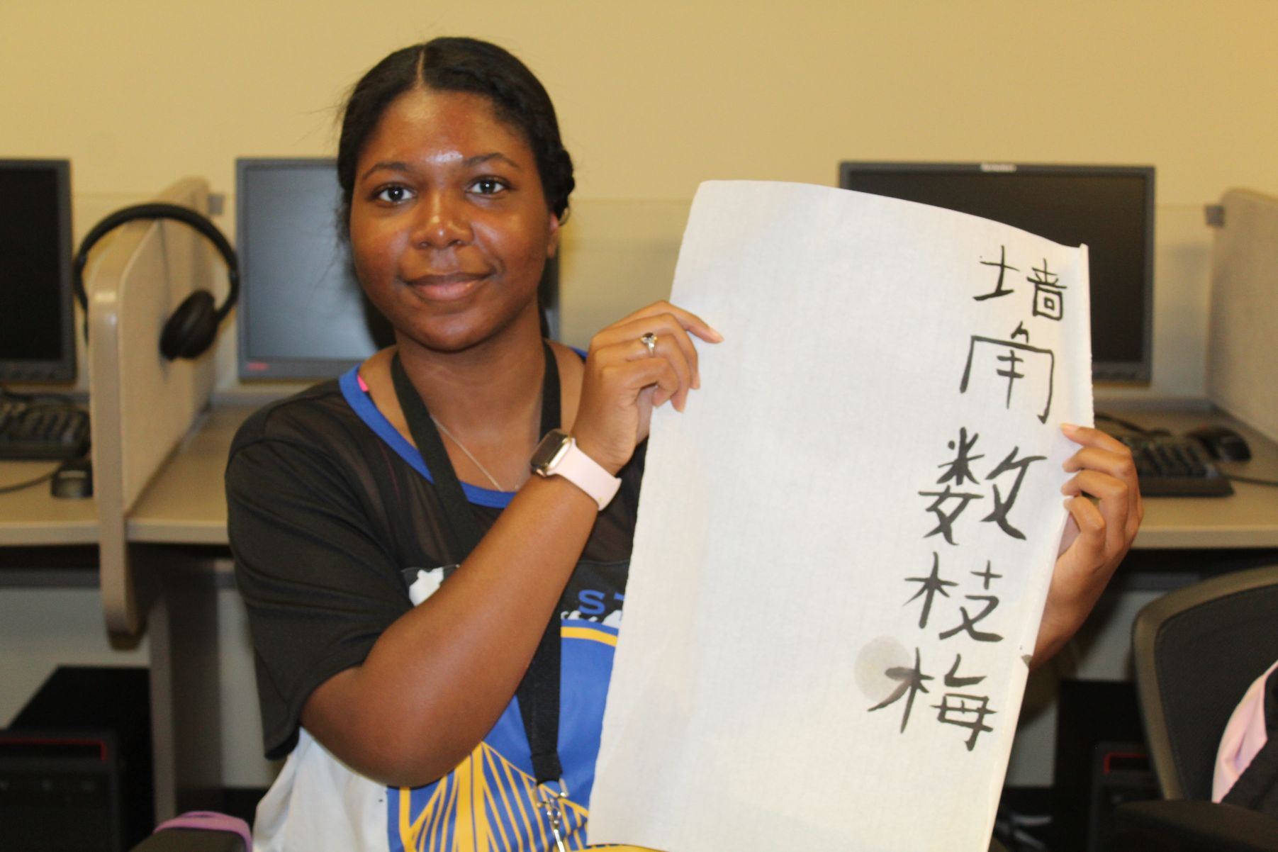 A proud student shows off her calligraphy.