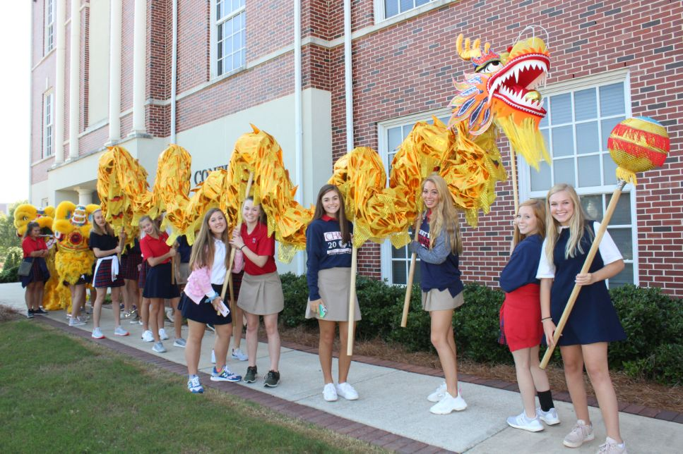 The girl students participate in the Dragon Dance.