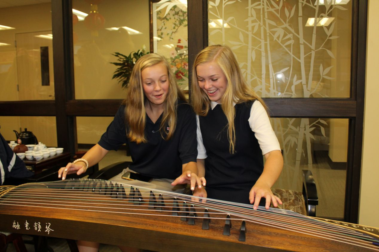 Two young girls play with the Guzheng, or Chinese zither, on display.