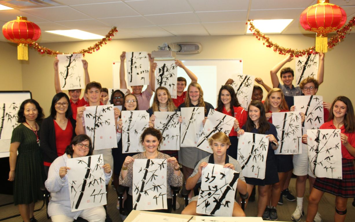 The students pose with their paintings proudly displayed with the CIT scholars.