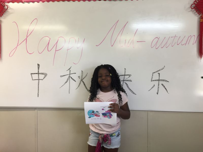 Proud student displays Mid-Autumn festival drawing.