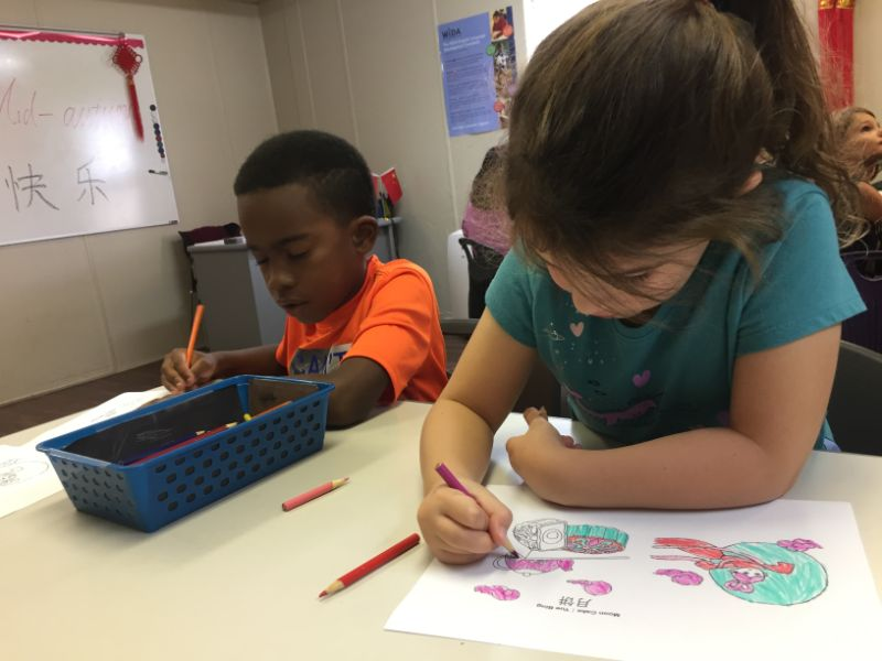 Two students use colored pencils to fill in the Mid-Autumn worksheets.
