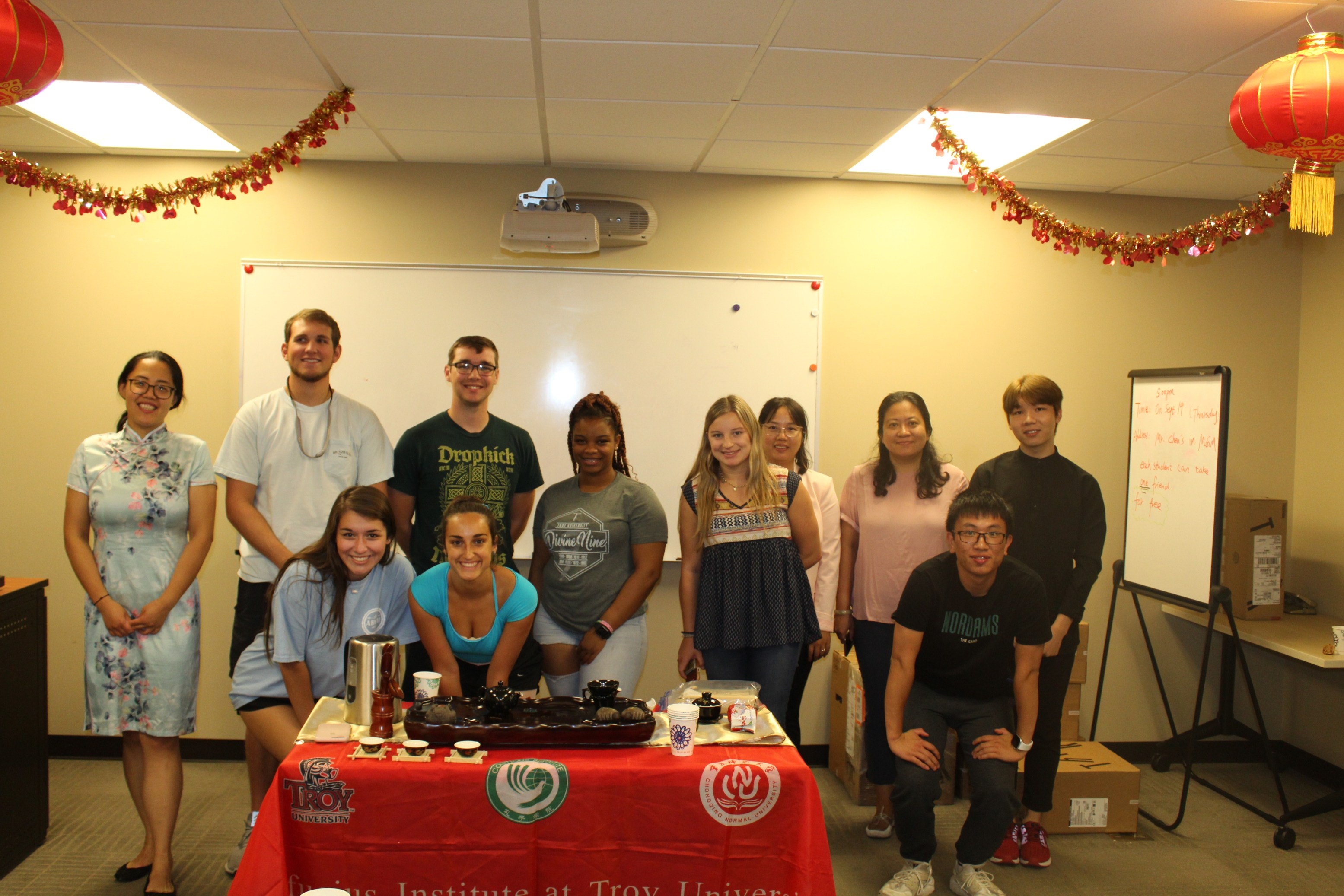 Students and Visiting Scholars pose together behind the Chinese Tea display.