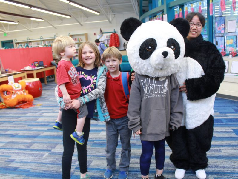 children took picture with panda suit