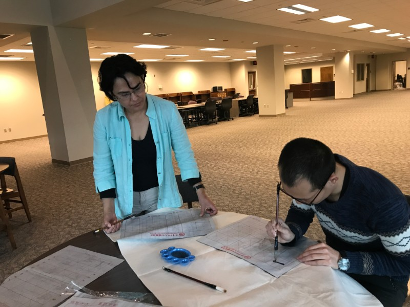 a visiting scholar showed the participant how to do chinese caligraphy