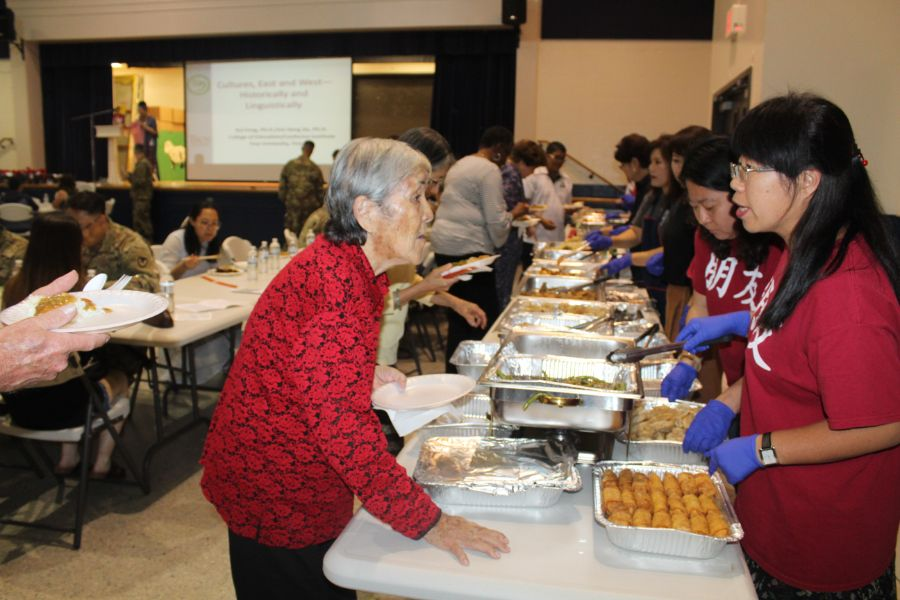 CIT staffs was serving Chinese cuisines to a senior.
