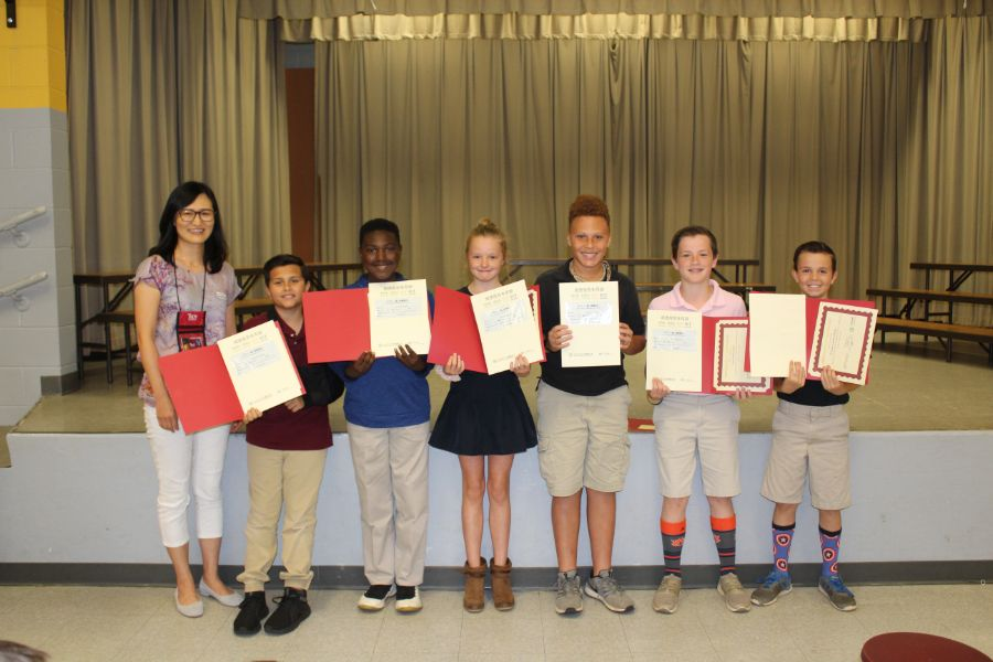 A group picture of visiting scholar and students from Kelly Spring Elementary school with their certificates.