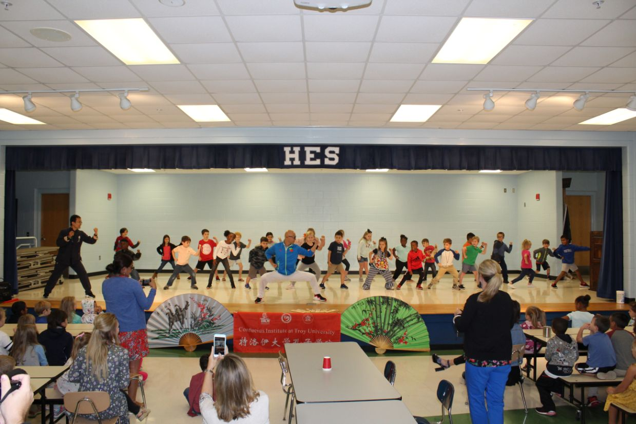 At Hillcrest Elementary School, the children practice Kung Fu on the stage together.