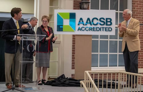 Sorrell College Dean Dr. Judson Edwards, left, is joined onstage by Chancellor Hawkins, right, Senior Vice Chancellor for Academic Affairs Dr. Earl Ingram,  and Trustee Karen Carter to announce the college's accreditation through AACSB, earning the University elite status among business schools.