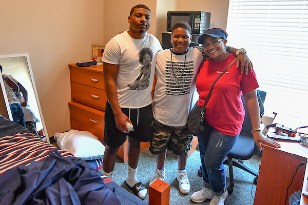 Freshman Jarrod Alexander from Newnan, GA poses with mom, Jennifer and his brother Jacob as he settles in to his new room.