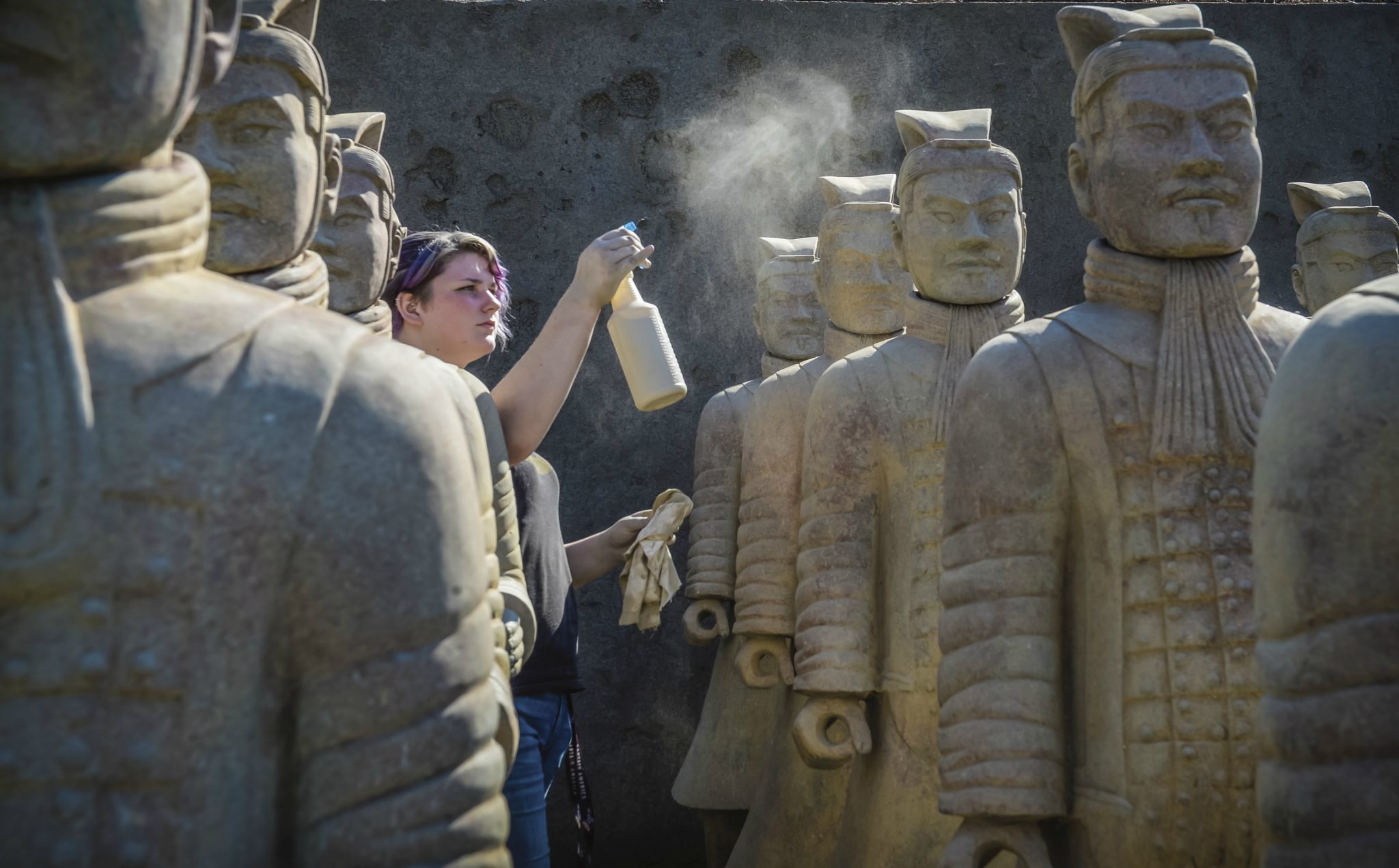 TROY student preparing terra cotta warriors for installation.
