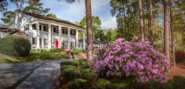 Pink azaleas and a beautifully landscaped lawn surrounds the driveway in front of the Chancellor's two-story residence that is accented with six white columns and a red door.