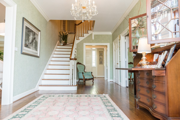 Looking from the front door, a beautiful staircase leads to the second floor, while a secretary's desk, green and pink rug and chair decorate the hallway.