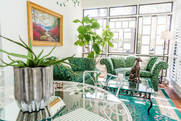 A view inside the sun room reveals green floral love seats, green floral accent rug and a clear round rod iron table.