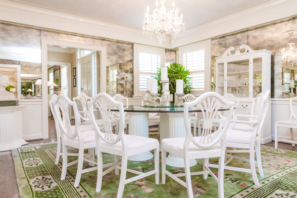 A glass-top, round dining table is surrounded by white-floral cushioned chairs set underneath a hanging crystal chandelier and accented by a white china cabinet with crystal.