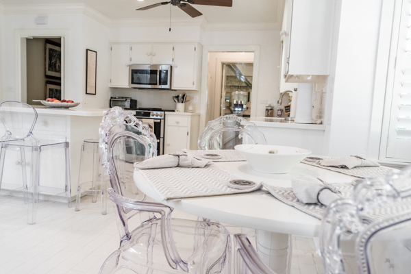 A view from the eat-in, white breakfast room table with acryllic chairs through to the kitchen inside the residence of the Chancellor of Troy University.