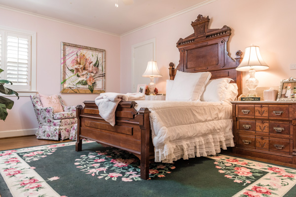 A centered cherry wood bed, along with cherry nightstands adorn the wall when you peer in to the pink-painted bedroom decorated with a green and pink floral rug and floral chair.