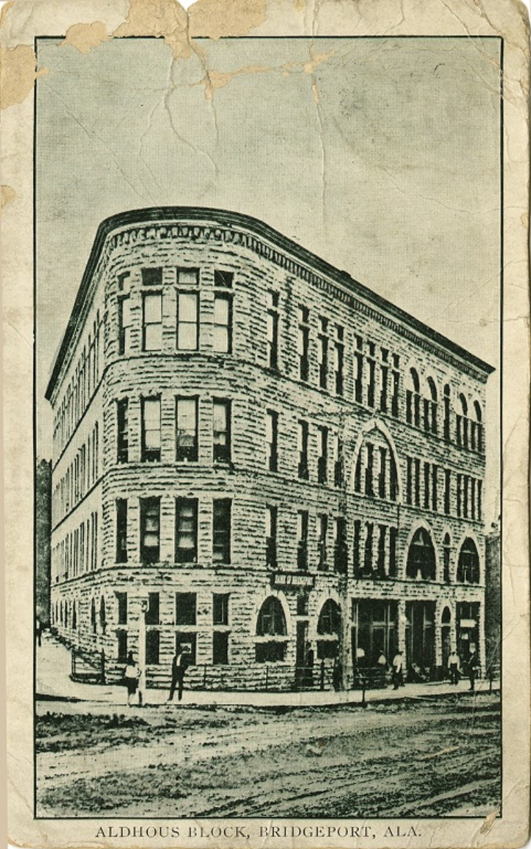 Black and white print of a multi-story building called Aldhous Block in Bridgeport, Alabama. Postmarked June 21, 1913.