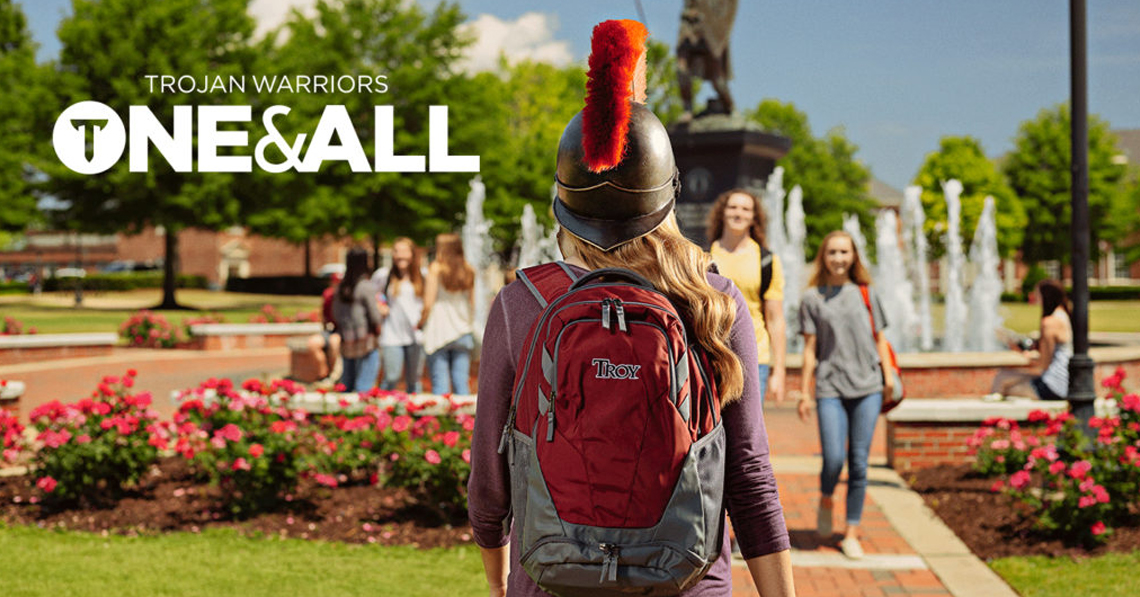 Trojan Warriors One & All, TROY student in helmet walking toward a fountain on the quad of the Troy, Alabama campus