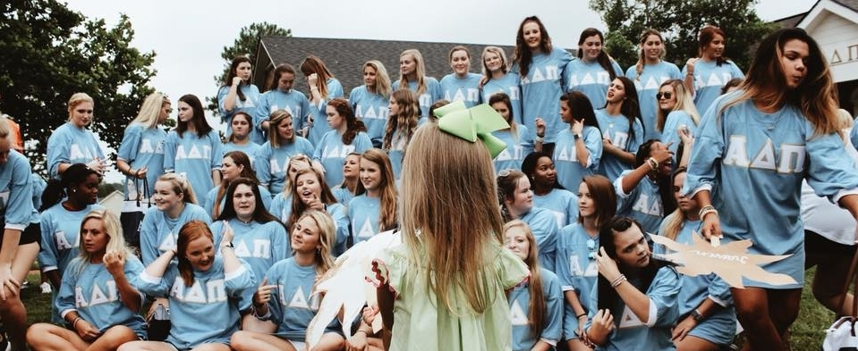 Little girl in front of Alpha Delta Pi sisters at Troy University