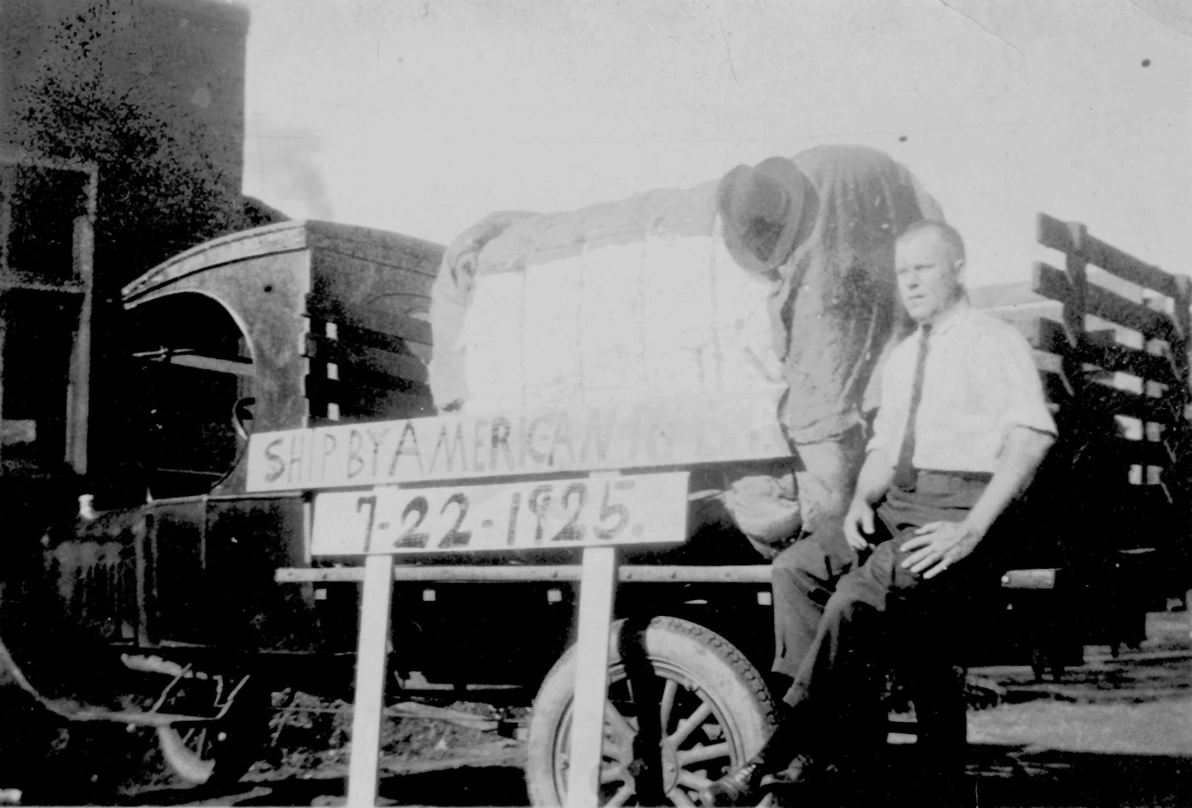 Henry W. Arnold, Sr., sitting on bed of Ford truck with bale of cotton