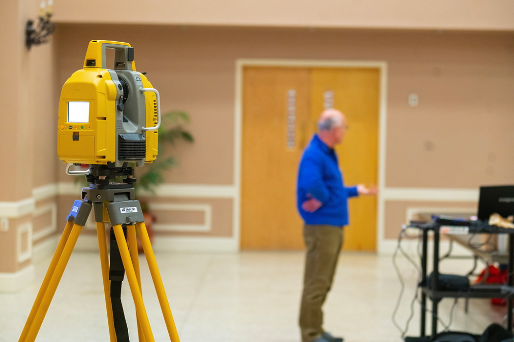 Professional discusses surveying with an electronic/optical instrument used for surveying and building construction on display during a Geo Day session