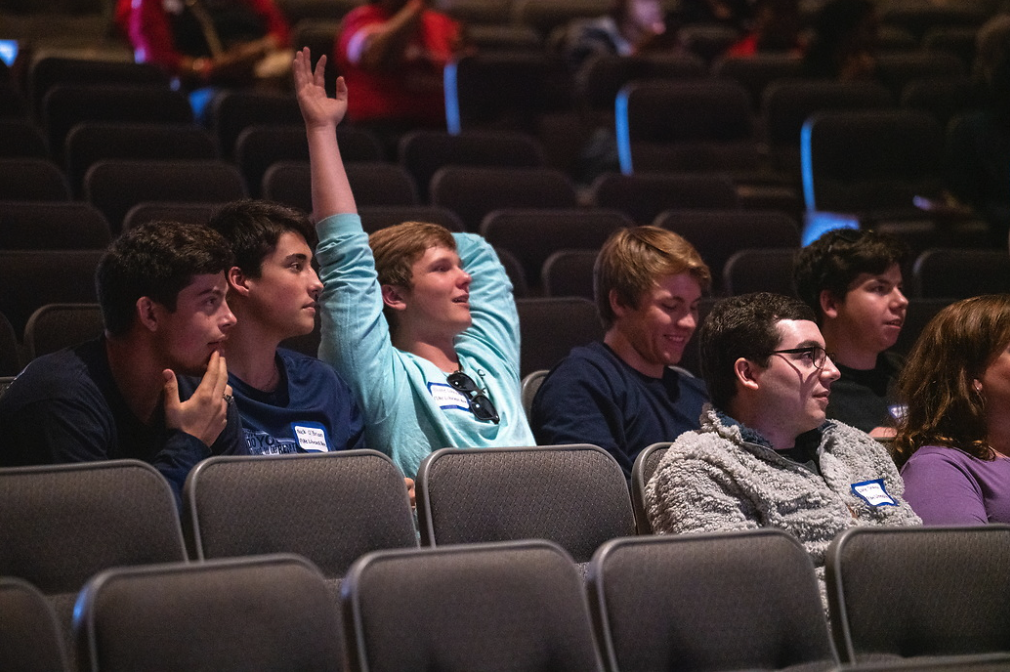 High school student raises his hand to answer questions during Geo Day closing session